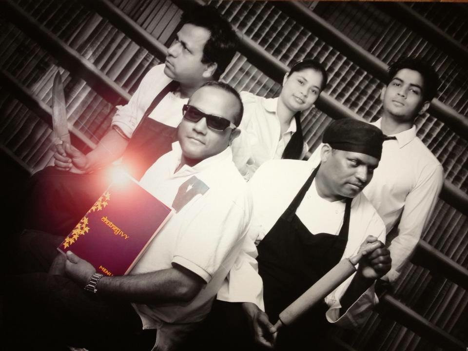 Chefs pose with kitchen utensils in a library in black and white