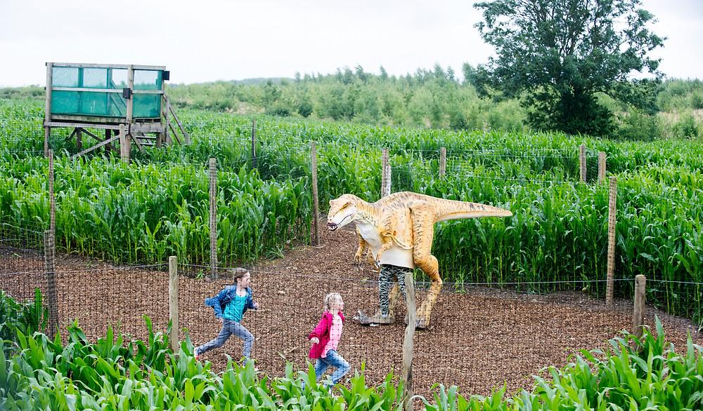 Orange dinosaur chasing two children in a maze