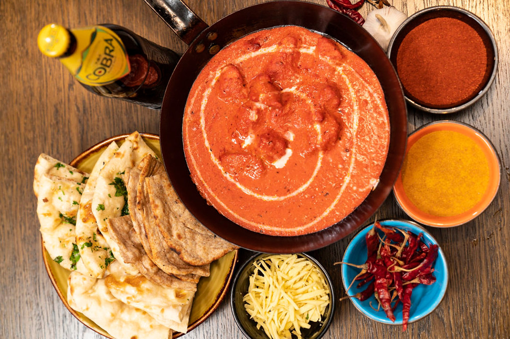 Beer, naan bread, curry and side dishes on a table
