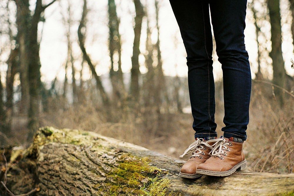 A person standing on a log in the woods wearing walking boots