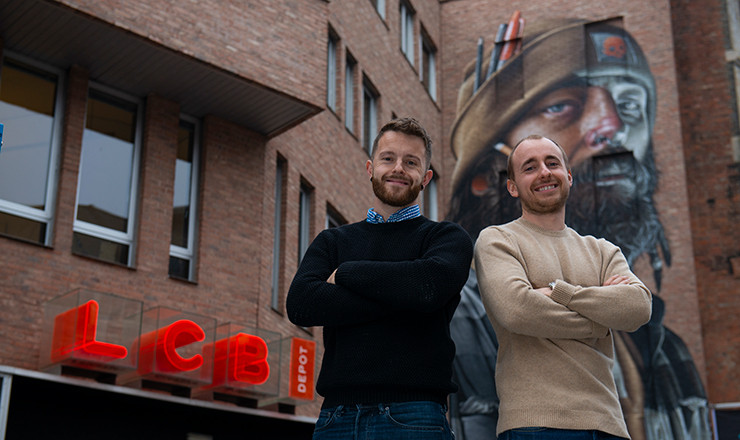 two men smiling stand in front of building with graffiti artwork and red LCB Depot sign