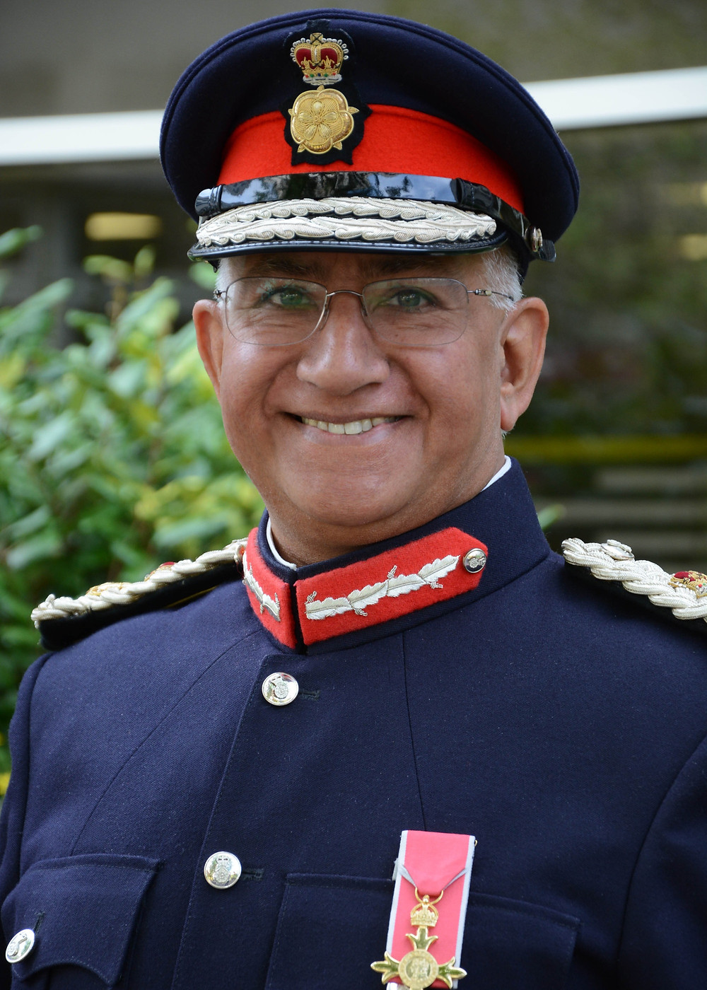 Her Majesty's Lord Lieutenant for Leicestershire, Mike Kapur OBE smiling in uniform with medal