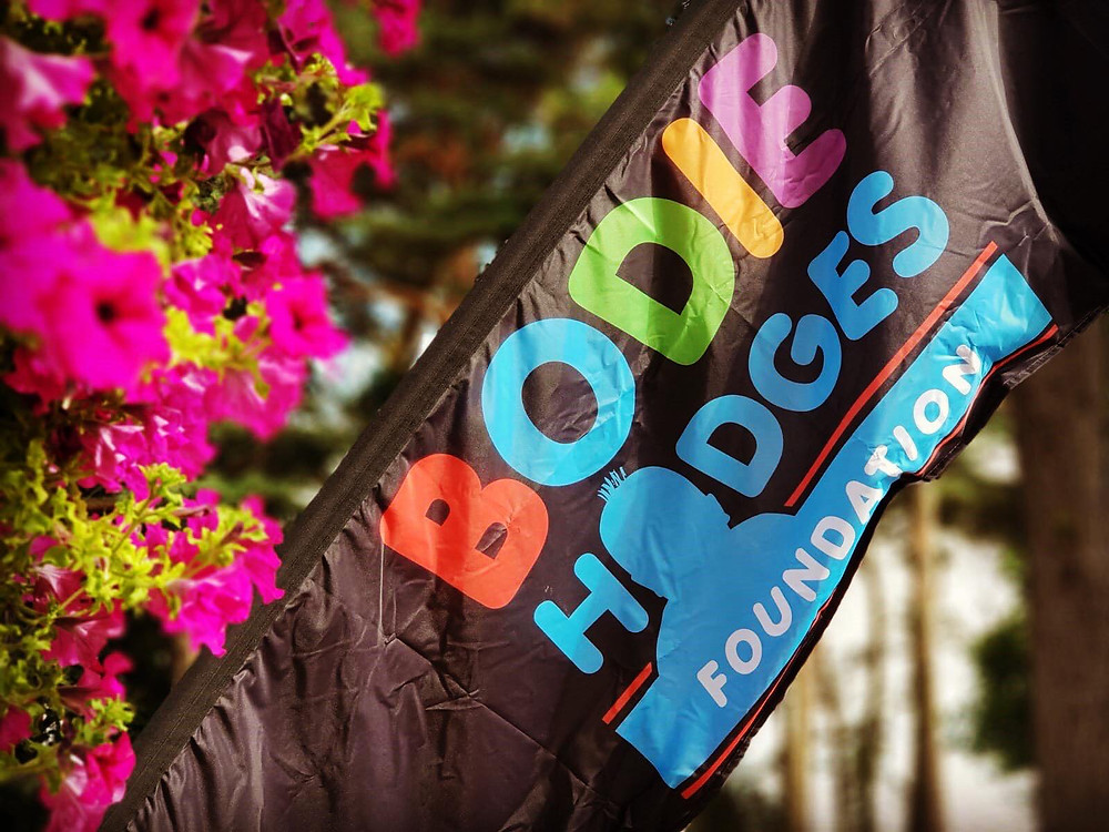 Pink flowers and a black flag with the Bodie Hodges Foundation logo