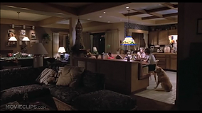 Screenshot from the film ET showing Elliot and his family eating dinner, with the dog on the right.
