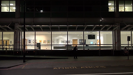 Night time shot of the exterior of UCH with a figure standing in the centre, looking at their phone.