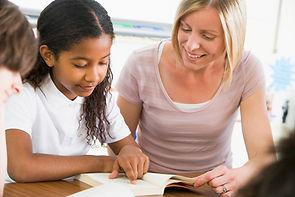 Adulte aidant une enfant à apprendre à lire