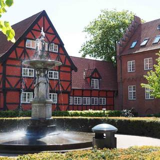 Ein rotes Fachwerkhaus mit Brunnen