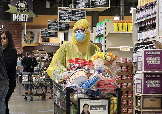 A woman in yellow protective gear pushes a shopping cart in a grocery store.