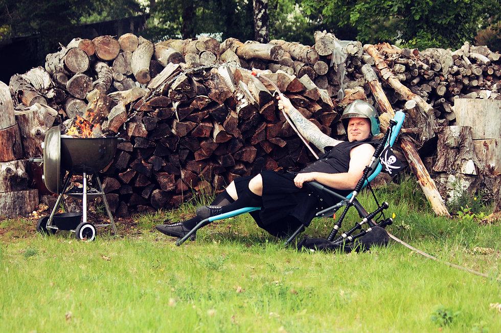Scotch Mac Vrillé avec un casque de pompier, allongé sur un transat qui éteint un feu dans un barbecue avec un tuyau d'arrosage