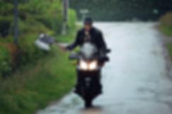 Charly Mac Vrillé sur une moto, tenant une basse en forme de hâche