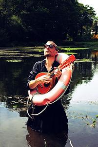 Toujouraléssè Mac Vrillé dans un étang avec une bouée de survie et une mandoline
