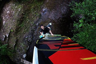 Soufflette Mac Vrillé qui fait de la planche à voile dans un ruisseau, avec sa bombarde entre les dents