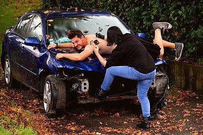 Kiki Mac Vrillé alongé sur une voiture cassée, en train de se faire tatouer le logo des vrillés sur l'épaule