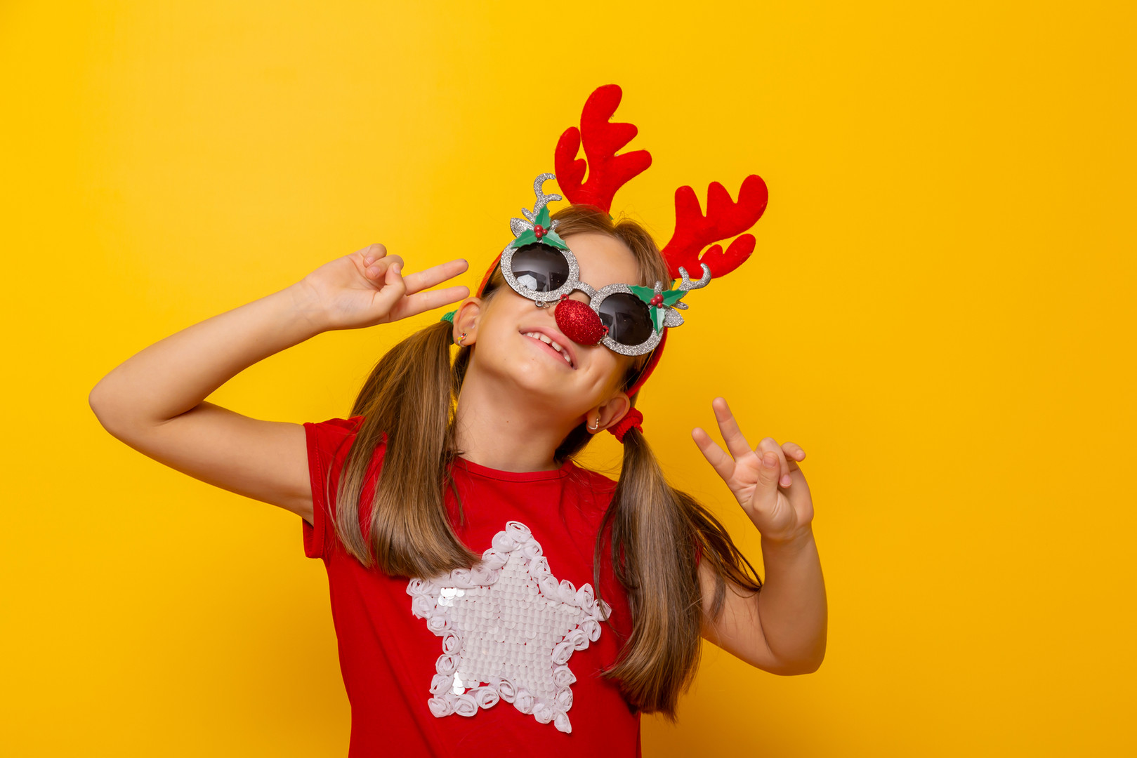 Little girl wearing party glasses with r
