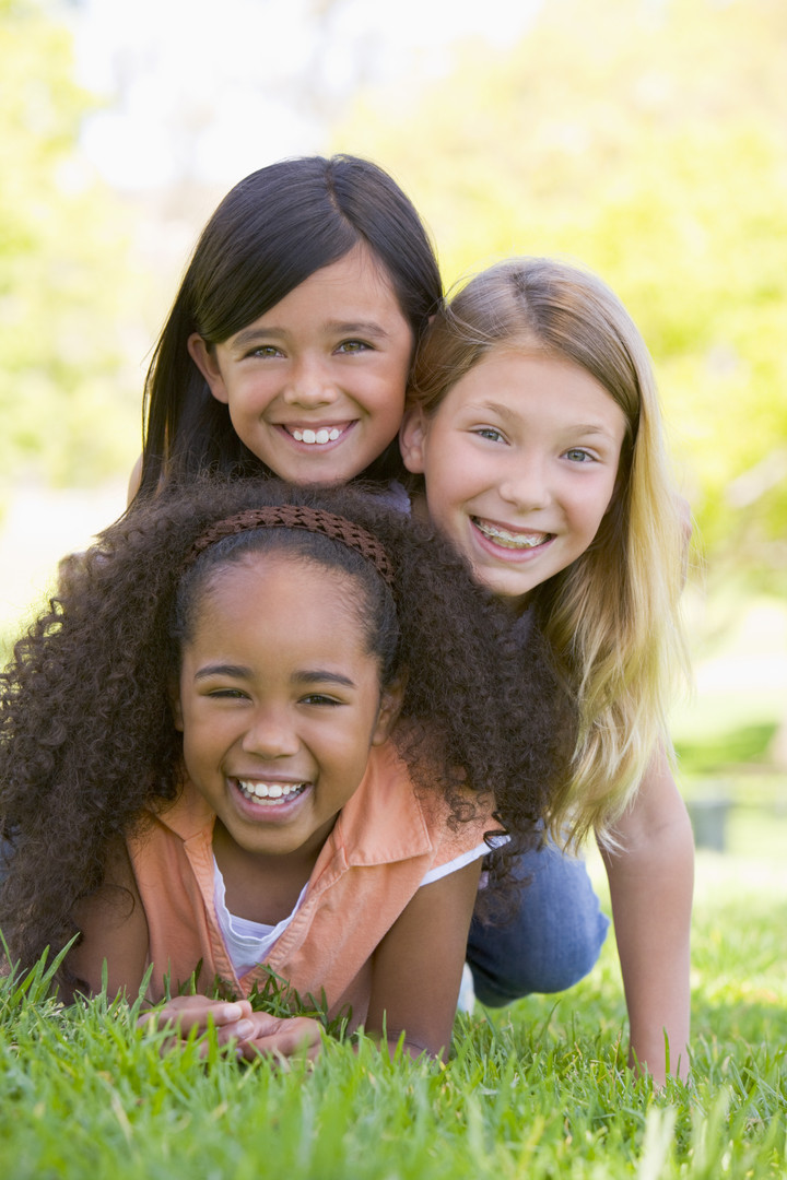 Three young girl friends piled up on top