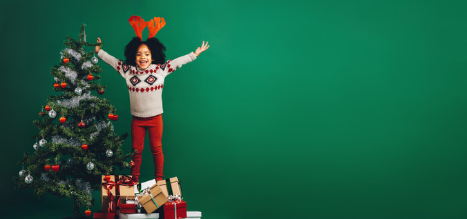 Happy little girl standing on gift boxes