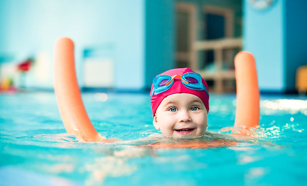 A young happy child swimming with a float in an indoor swimming pool