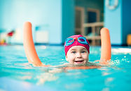 Young girl in a pink swim cap hanging onto a pool noodle while swimming