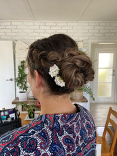 Bridal braided Chignon with flower accents for medium length, medium thickness hair.