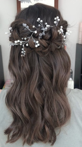 Dreamy twisted half up half down with hair piece (provided by client) for the bride.