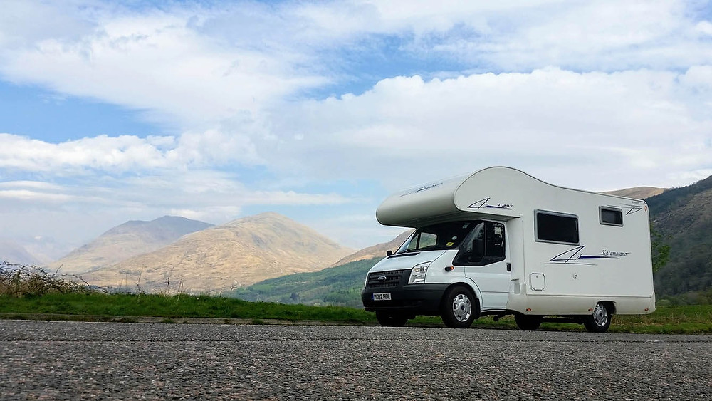 White rimor motorhome in front of the Scottish highlands under a blue and cloudy sky.