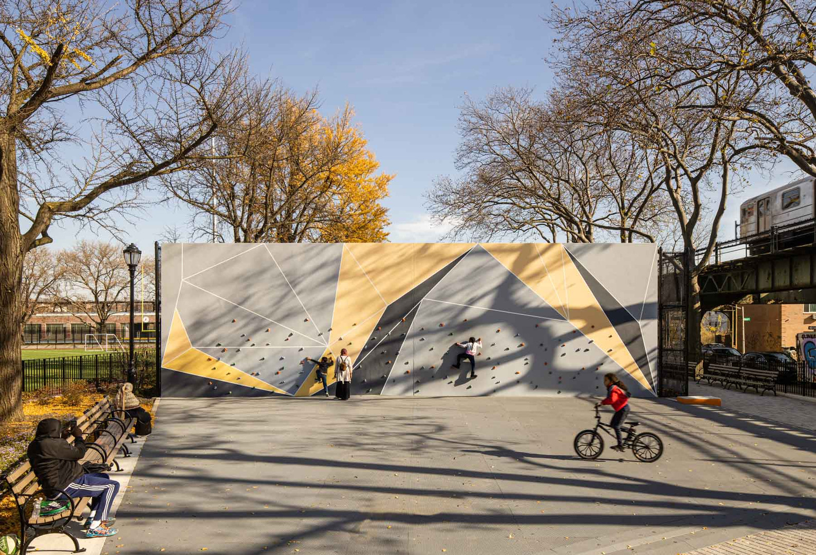 A climbing wall with geometric shapes offer a unique way to exercise on a repurposed handball court.