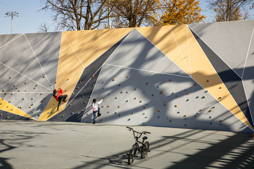 One side of an existing handball wall was re-imagined as a colorful and challenging traverse wall; the opposite side serves as two handball courts.