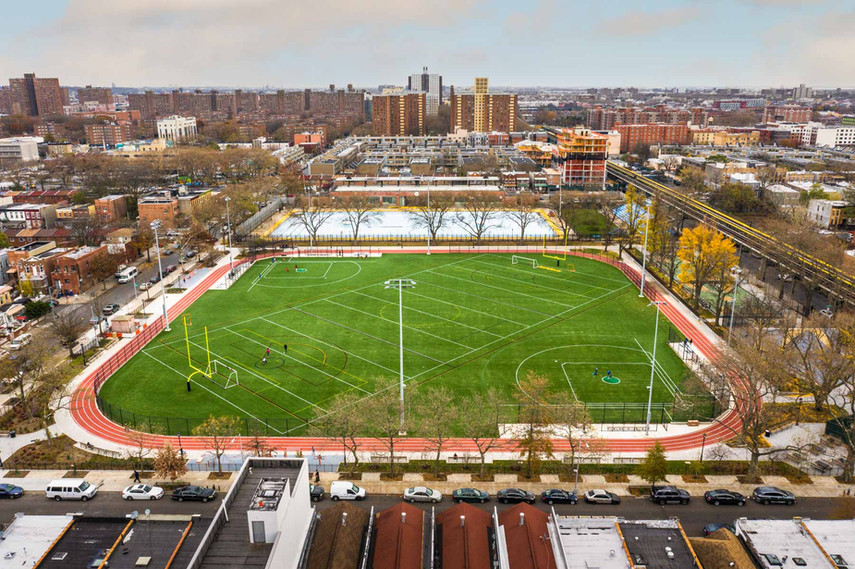 Aerial view overlooking the massive 129,000-square-foot, multi-sport synthetic turf field and recreational running track nestled in the heart of Brownsville. The brand-new synthetic turf field replaced a natural turf field and accommodates softball, football, soccer, and boy's and girl's lacrosse.