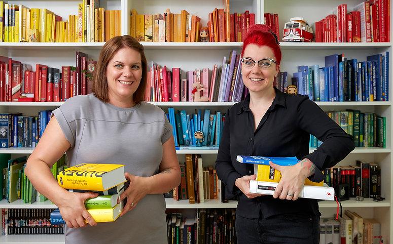 Das letzte Auge; Ilse Vogt und Claudia Bartholdi stehen vor einem bunten Bücherregal mit Duden und anderen Wörterbüchern