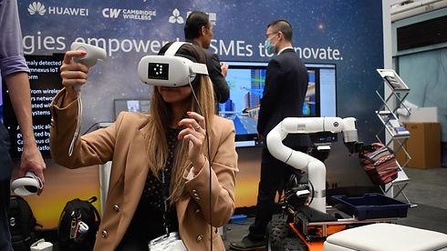 Woman operating VR SenseKit controlling robotic arm remotely