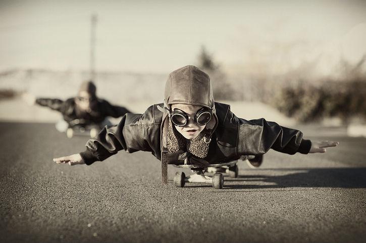 Child wearing pilot glasses pretentding to fly on skateboard