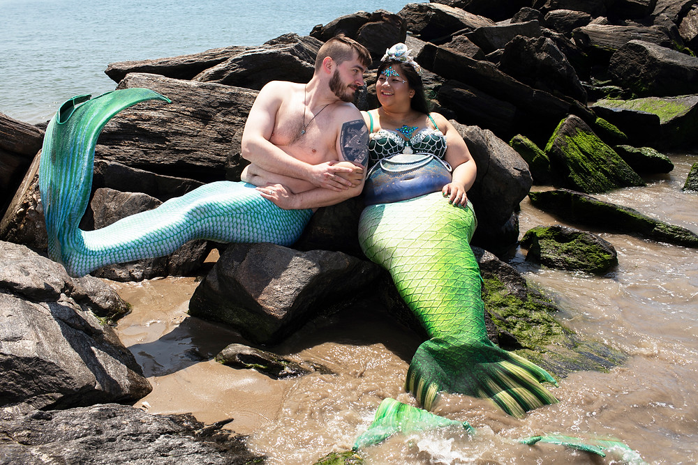 two merpeople sitting on a rock.  One is pregnant.  The merman is flipping his tail