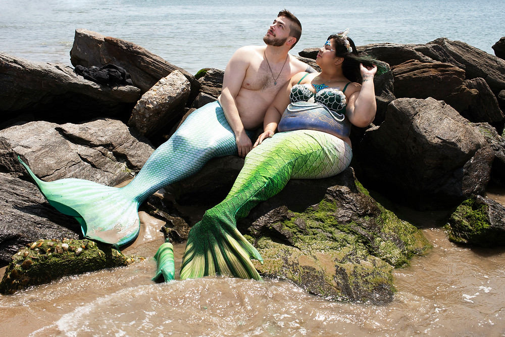 two merpeople sitting on a rock.  One is pregnant.