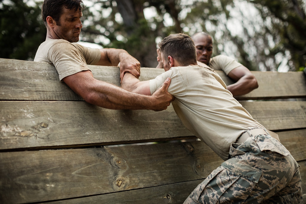 Soldiers helping man to climb wooden wal