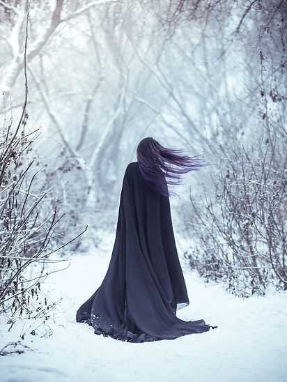 Lady in Black Cape in snow from behind.j