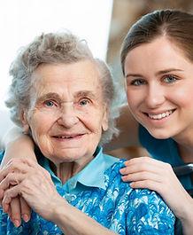 Elderly lady with young nurse smilingat camera