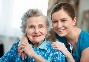 elderly diabled woman in chair smiling while a yonger Direct Support Professional is slightly hugging her smiling. The elderly woman holds the hand of the younger woman with comfort.