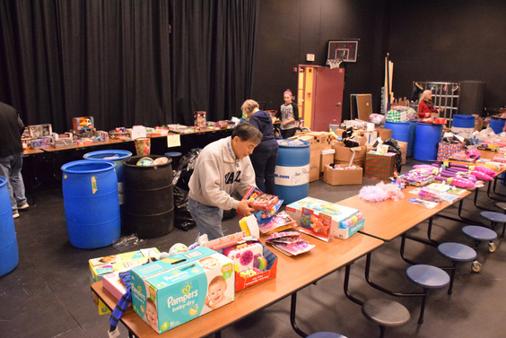 Volunteers helping sort and wrap gifts.