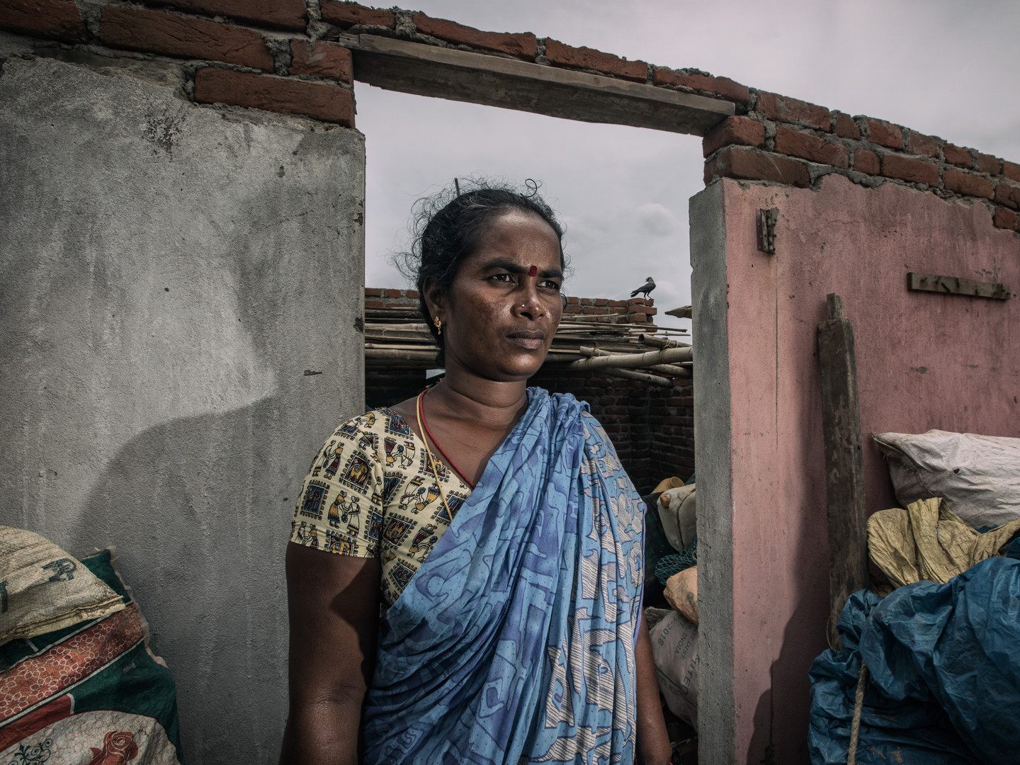 Indian woman in her destroyed house