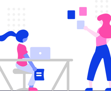 Two women collaborating in a tech education workshop.