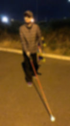 Picture shows Victoria walking along with her red cane and skateboard under her arm at night.