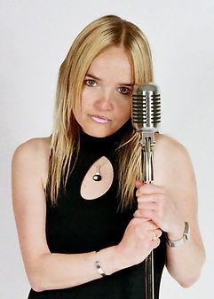 Victoria wearing a black dress holding a jazz microphone