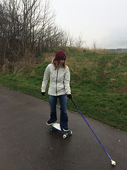 Picture of Victoria Claire skating on her skateboard using her purple mobility long cane in her left hand to navigate.
