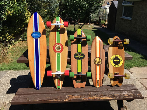 5 Blinded Soul Skateboards lined up in a row, from left to right, longboard with blue and white stripe, longboard with green, red and white stripes, cruiser single kick with green and black stripe, mini cruiser dark wood with brown and cream stripe and retro fish tail cruiser with brown and yellow artwork