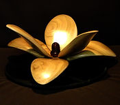 Picture of a sculpture of a wooden magnola flower, its petals splayed out in 2 layers.