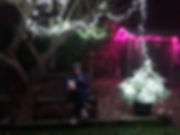 Picture of Victoria and Ralf sitting under the Christmas lights in the garden.