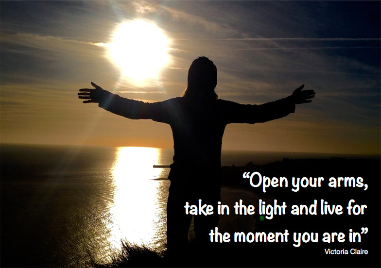 Photo of person standing on a cliff top they are back lit by the sun as it bounces off the ocean below, quote reads open your arms, take in the light and live for the moment you are in, Victoria Claire.