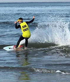 Kai Owens riding his skimboard wearing a yellow vest over his wetsuit that has the words blind athlete on it.
