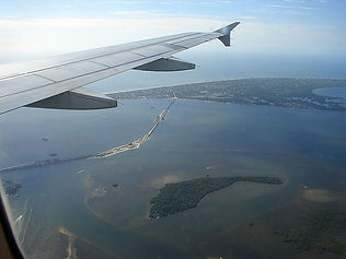 A view from the window of a plane as it flies over an island with a long bridge.