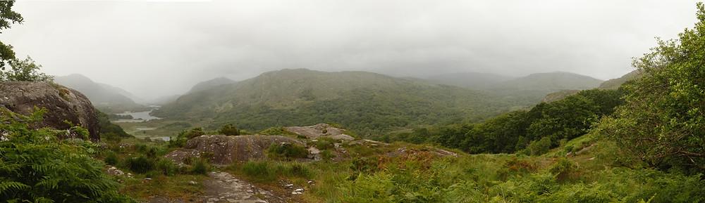 Green hills, brown rocks and mist-shrouded hills